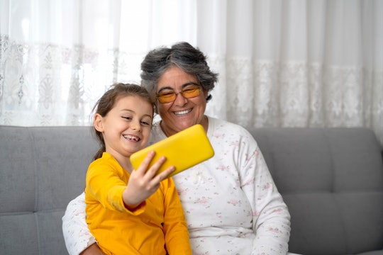 Adorable little girl making selfie with happy nanny grandma at home. They are sitting on a sofa in living room.