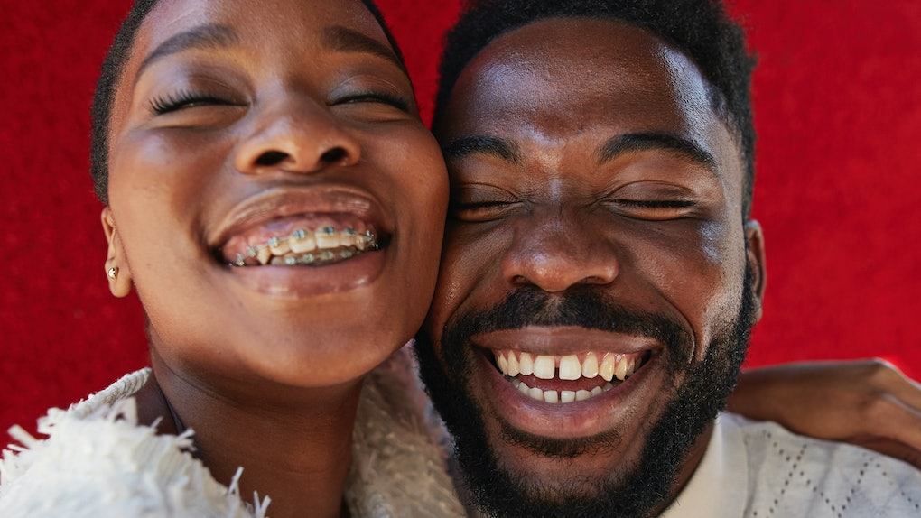 Smiling male and female friend with eyes closed against red wall