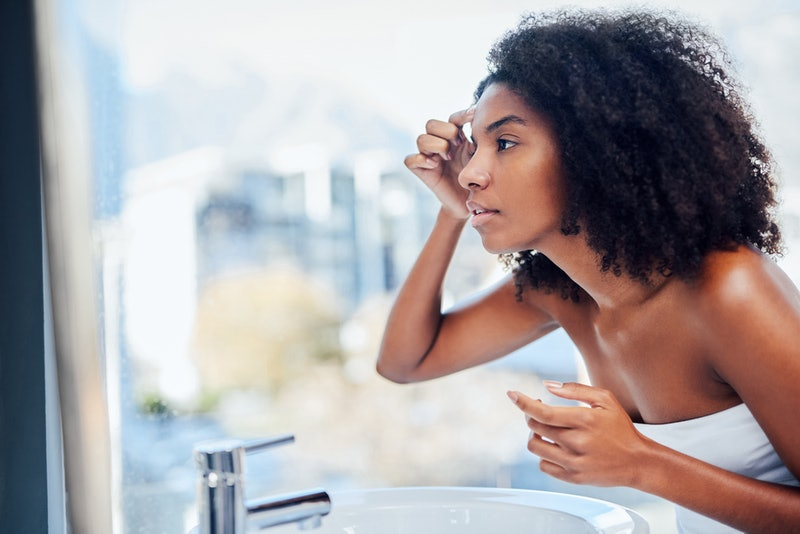 A person with natural hair wears a white towel in the bathroom while checking their face in the mirror. Stress can't give you eczema, but anxiety can cause a flare-up.