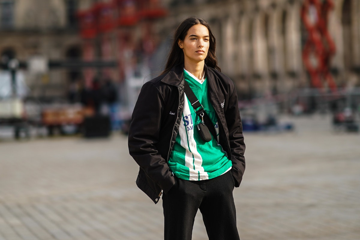 PARIS, FRANCE - MARCH 09: A model wears a a black jacket, a green and white stripe v-neck soccer t-s...