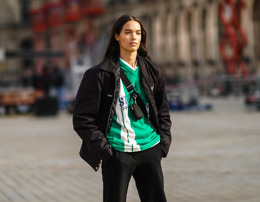 PARIS, FRANCE - MARCH 09: A model wears a a black jacket, a green and white stripe v-neck soccer t-shirt, a mini fanny pack bag crossbody, black pants, on March 09, 2021 in Paris, France. (Photo by Edward Berthelot/Getty Images)