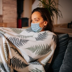 A person sits on their couch, covered in a blanket while wearing a mask. If your friend has COVID, there are ways to check on them safely.