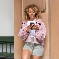 A young and fashionable mixed race woman uses her mobile phone while outside city building. She is leaning against a wall casually and appears to be waiting for a taxi or ride share service.