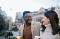 Happy young diverse romantic couple on a vacation, exploring the city on foot,  having fun and enjoy...