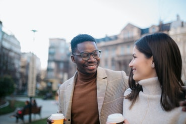 Happy young diverse romantic couple on a vacation, exploring the city on foot,  having fun and enjoying a cup of coffee, smiling