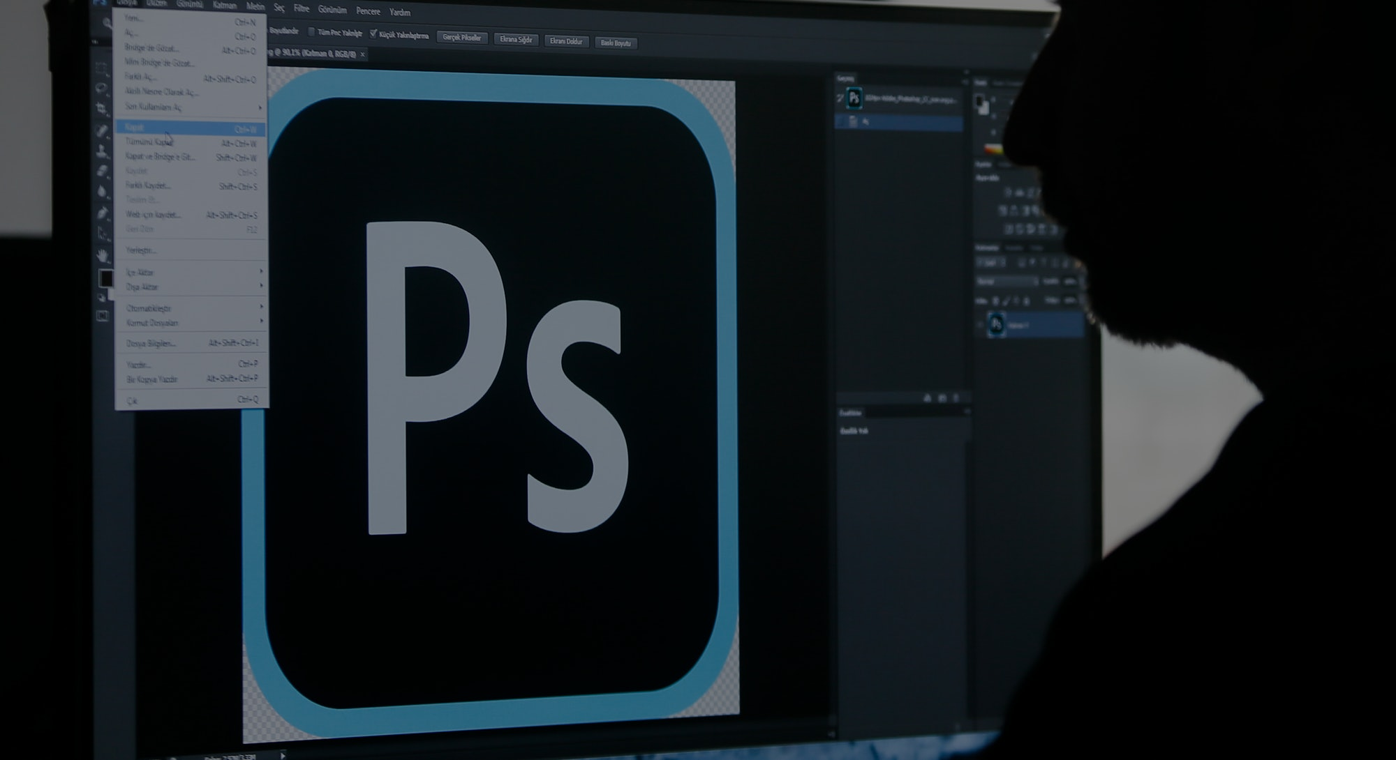 A person sitting at a computer using Photoshop.