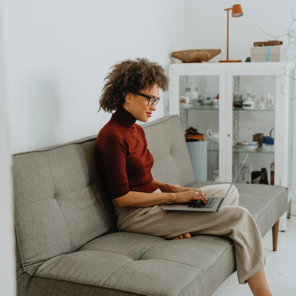 A woman works on a grey couch. 11 women explain how they're observing the anniversary of COVID lockd...