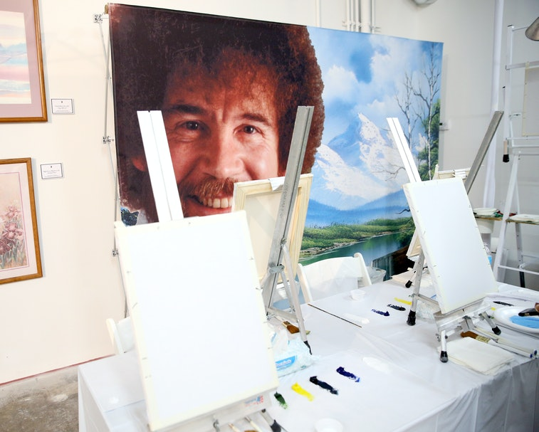 A large sized painting of Bob Ross is seen in a studio.