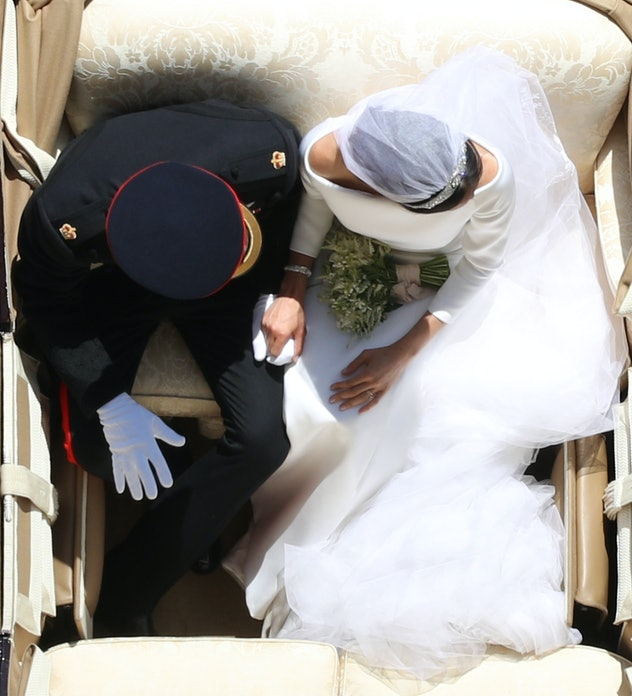 In the royal carriage the couple held hands on their wedding day.