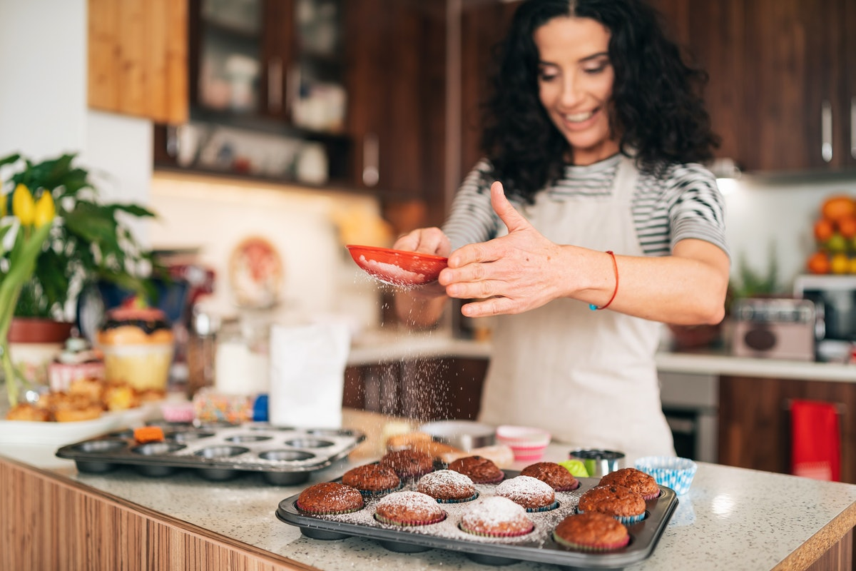 A smiling woman coats muffins in powdered sugar in her kitchen.