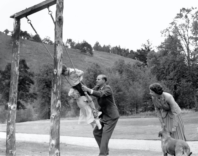 Prince Philip pushes his children on a swing, 1955.