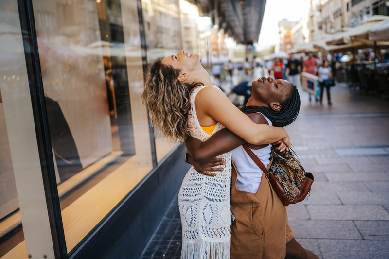 Two friends hug outside while not wearing masks. Experts explain how we will know when the pandemic in the u.s. is over.