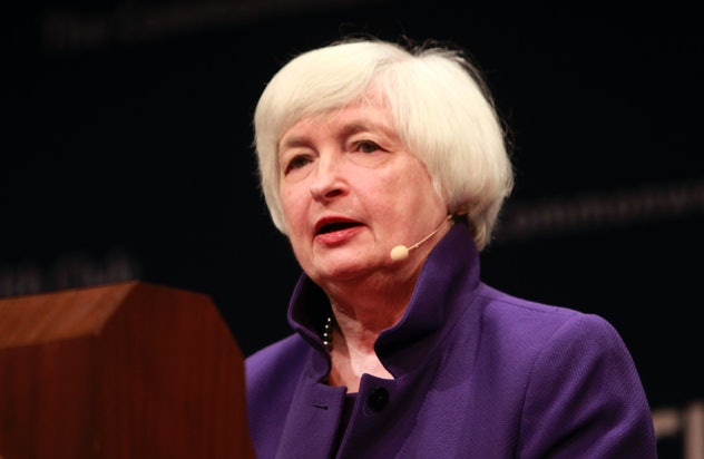 Dr. Janet Yellen wears a purple shirt and stands behind a podium.