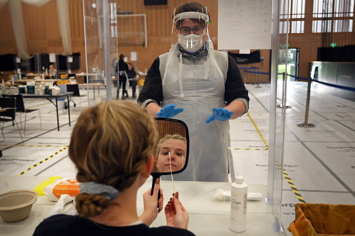 A medical worker in protective gear helps a young woman holding a mirror with a COVID-19 test