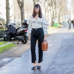 PARIS, FRANCE - MARCH 02: Evangeline Smyrotaki wearing a white top, black denim jeans, brown bag, ou...