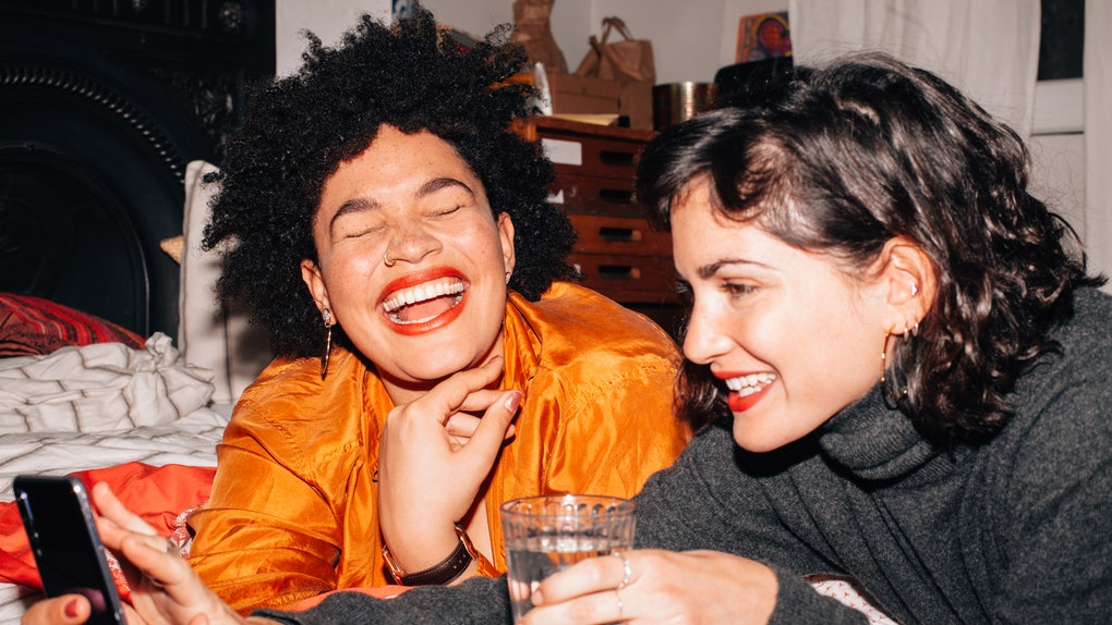 Two young women laugh while creating BFF Pinterest boards for each other.