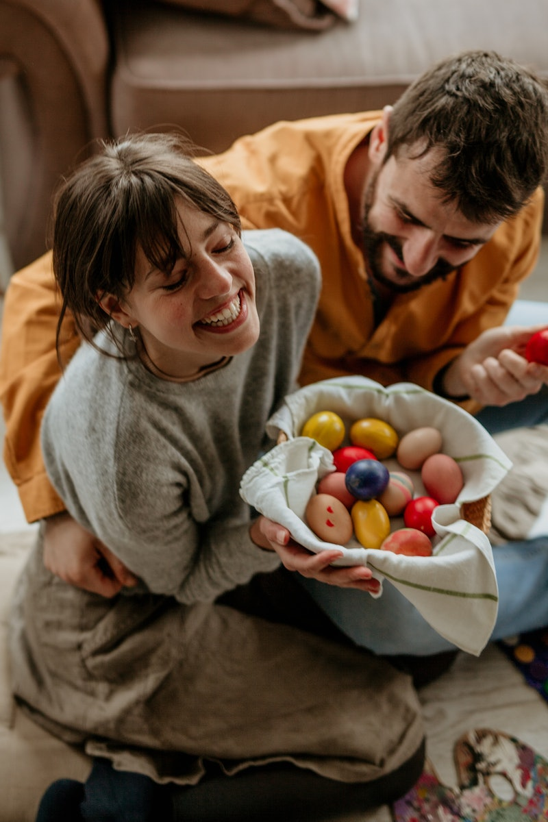 Top view of a loving couple painting Easter eggs in a cozy living room, crate full of colorful eggs next to them. Easter and painting concept.