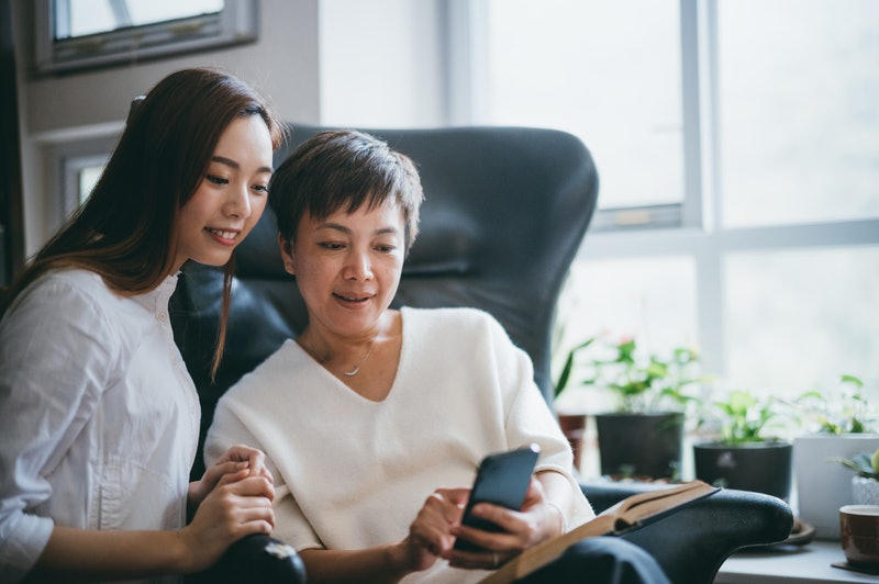 Asian mother and daughter having fun while using smartphone together at home