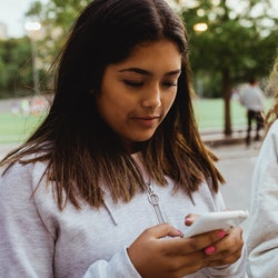 A girl in a white sweater texts a friend to help her feel better with help from therapists.