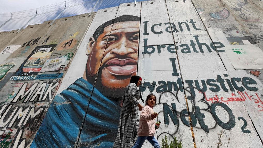 "People walk past a mural showing the face of George Floyd, an unarmed handcuffed black man who died after a white policeman knelt on his neck during an arrest in the US, painted on a section of Israel's controversial separation barrier in the city of Bethlehem in the occupied West Bank on March 31, 2021. - The teenager who took the viral video of George Floyd's death said on March 30, at the trial of the white police officer charged with killing the 46-year-old Black man that she knew at the time ""it wasn't right."" Darnella Frazier, 18, was among the witnesses who gave emotional testimony on Tuesday at the high-profile trial of former Minneapolis police officer Derek Chauvin. Chauvin, 45, is charged with murder and manslaughter for his role in Floyd's May 25, 2020 death, which was captured on video by Frazier and seen by millions, sparking anti-racism protests around the globe. In the video, Chauvin, who was subsequently fired from the police department, is seen kneeling on the neck of a handcuffed Floyd for more than nine minutes. (Photo by Emmanuel DUNAND / AFP) (Photo by EMMANUEL DUNAND/AFP via Getty Images)"