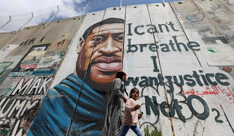 """People walk past a mural showing the face of George Floyd, an unarmed handcuffed black man who died after a white policeman knelt on his neck during an arrest in the US, painted on a section of Israel's controversial separation barrier in the city of Bethlehem in the occupied West Bank on March 31, 2021. - The teenager who took the viral video of George Floyd's death said on March 30, at the trial of the white police officer charged with killing the 46-year-old Black man that she knew at the time """"it wasn't right."""" Darnella Frazier, 18, was among the witnesses who gave emotional testimony on Tuesday at the high-profile trial of former Minneapolis police officer Derek Chauvin. Chauvin, 45, is charged with murder and manslaughter for his role in Floyd's May 25, 2020 death, which was captured on video by Frazier and seen by millions, sparking anti-racism protests around the globe. In the video, Chauvin, who was subsequently fired from the police department, is seen kneeling on the neck of a handcuffed Floyd for more than nine minutes. (Photo by Emmanuel DUNAND / AFP) (Photo by EMMANUEL DUNAND/AFP via Getty Images)"""