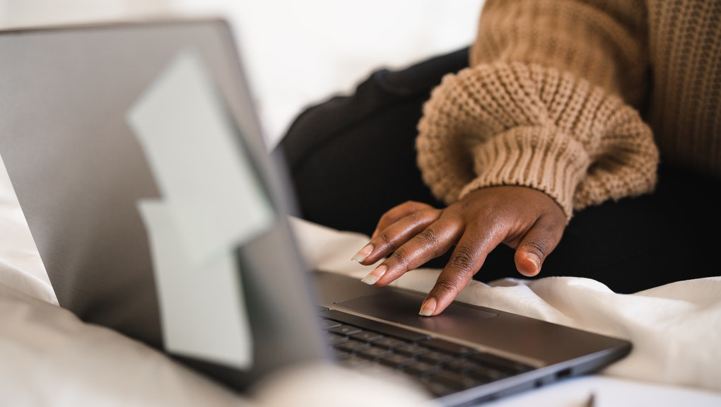 A female university student is sitting in her bed, studying on her laptop. She is working from home for social distancing purposes.