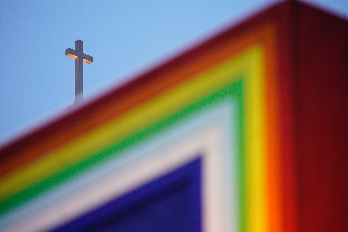 A rainbow colored sculpture is seen with a Cathohlic church cross in the background in Warsaw, Polan...