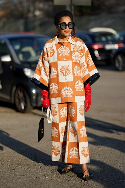 MILAN, ITALY - FEBRUARY 19: Tamu Mcpherson wears Gucci sunglasses with chains, a white and orange ch...