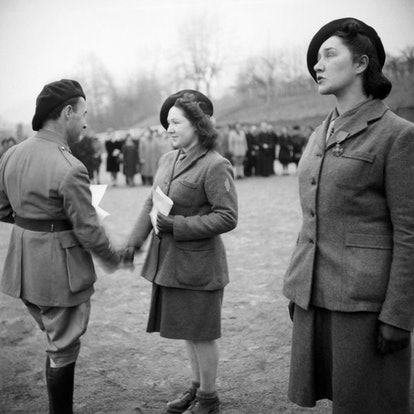 Xavier de Virieu (L) decorates with the Croix de Guerre young women during a military ceremony at the Uriage military school, in January 1945 in Uriage, near Grenoble. - The Ecole des cadres d'Uriage, located at the Uriage Castle near Grenoble and intended for training the French elites, was created under the Vichy regime by Dunoyer de Segonzac, then dissolved and replaced by the Militia executive school, and finally became at the Liberation the FFI executive military school, under the direction of Xavier de Virieu. (Photo by - / AFP) (Photo by -/AFP via Getty Images)