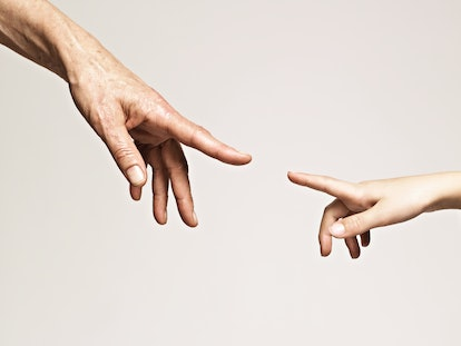 Young girl and older woman point index fingers to each other, nearly touching