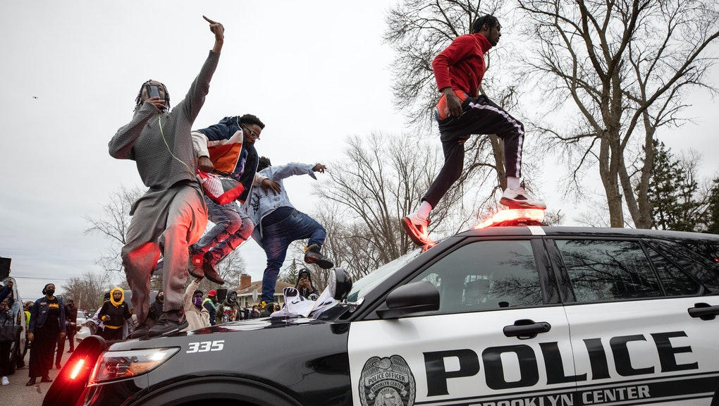 BROOKLYN CENTER, MN - APRIL 11: Men jumped on police vehicles near the site of an officer involved shooting and killing of Daunte Wright during a traffic stop. (Photo by Carlos Gonzalez/Star Tribune via Getty Images)