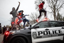 BROOKLYN CENTER, MN - APRIL 11: Men jumped on police vehicles near the site of an officer involved s...