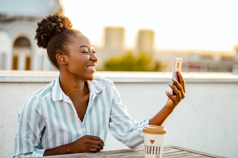 Young African American woman is on the balcony at sunset, she is talking to someone over video call