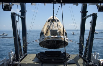 GULF OF MEXICO - AUGUST 2: In this handout image provided by NASA, the SpaceX Crew Dragon capsule spacecraft, with NASA astronauts Robert Behnken and Douglas Hurley onboard, is lifted onto the SpaceX GO Navigator recovery ship after landing in the Gulf of Mexico on August 2, 2020 off the coast of Pensacola, Florida. The Demo-2 mission is the first launch with astronauts of the SpaceX Crew Dragon spacecraft and Falcon 9 rocket to the International Space Station as part of the agency's Commercial Crew Program. The test flight serves as an end-to-end demonstration of SpaceXs crew transportation system. Behnken and Hurley launched at 3:22 p.m. EDT on Saturday, May 30, from Launch Complex 39A at the Kennedy Space Center. A new era of human spaceflight is set to begin as American astronauts once again launch on an American rocket from American soil to low-Earth orbit for the first time since the conclusion of the Space Shuttle Program in 2011. (Photo by Bill Ingalls/NASA via Getty Images)