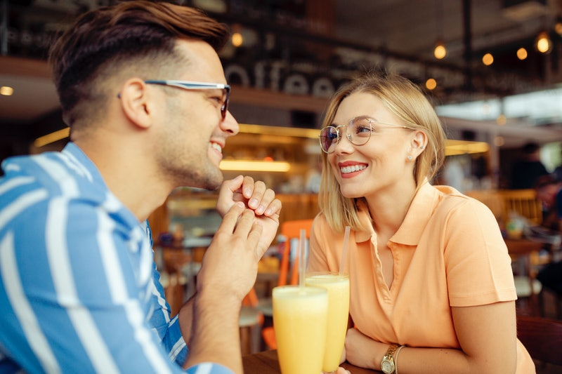 Happy Caucasian young couple having fun together, sitting in a coffee shop, smiling and enjoying the...