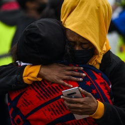 BROOKLYN CENTER, MN - APRIL 11: Two people embrace as demonstrators gather on April 11, 2021 in Brooklyn Center, Minnesota. Protesters took to the streets today after 20 year old Daunte Wright was shot and killed during a traffic stop by members of the Brooklyn Center police. (Photo by Stephen Maturen/Getty Images)