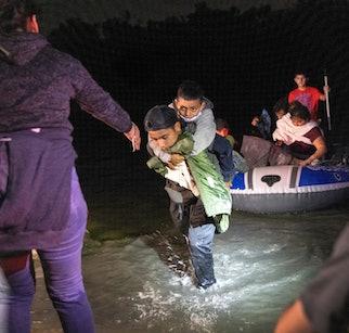 ROMA, TEXAS - APRIL 9: Boys walk onto shore after a smuggler rowed them across the Rio Grande at the...