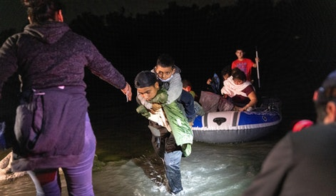 ROMA, TEXAS - APRIL 9: Boys walk onto shore after a smuggler rowed them across the Rio Grande at the U.S.-Mexico border on April 9, 2021 in Roma, Texas. A surge of immigrants crossing into the United States, including record numbers of children, continues along the southern border. (Photo by John Moore/Getty Images)