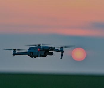 26 March 2021, Brandenburg, Sieversdorf: A DJI Mavic Air 2 quadrocopter (drone) flies over a field at sunset. Photo: Patrick Pleul/dpa-Zentralbild/ZB (Photo by Patrick Pleul/picture alliance via Getty Images)