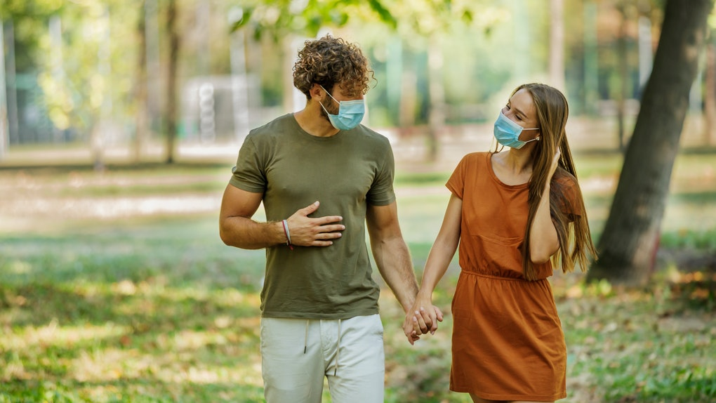 Portrait of Cheerful Young Couple with Face Masks who is Walking in the Park Path and Having a Nice Conversation in the Time of Corona Virus.