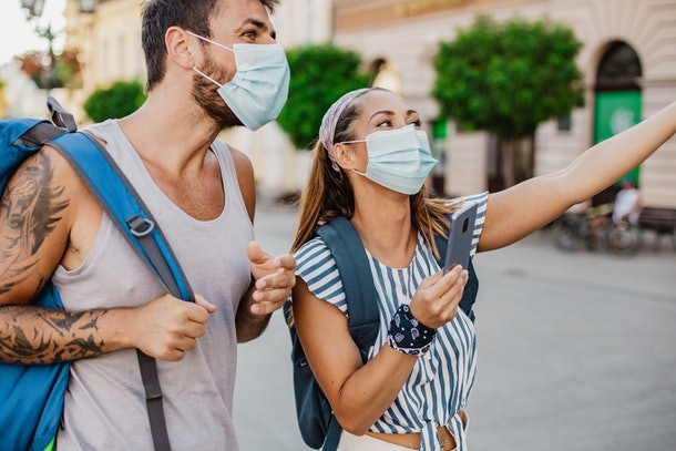 Two tourists wearing face masks and backpacks. They are walking and smiling