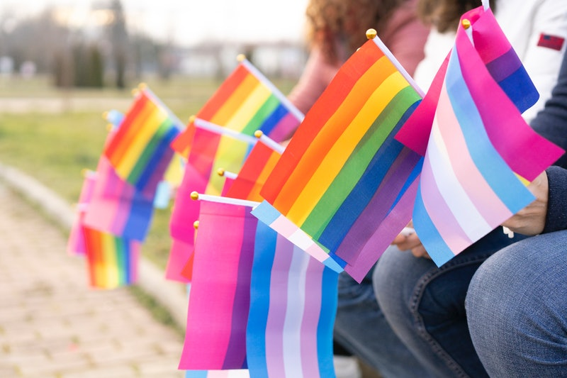 People sitting on a bench holding different flags for the protest defending the LGBTQ rights