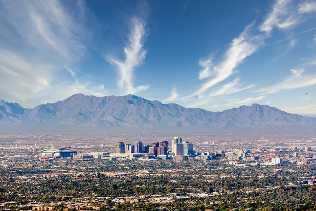 Looking south west to the tall buildings of Downtown Phoenix and South Mountain Preserve from Camelback Mountain in Maricopa County Arizona USA