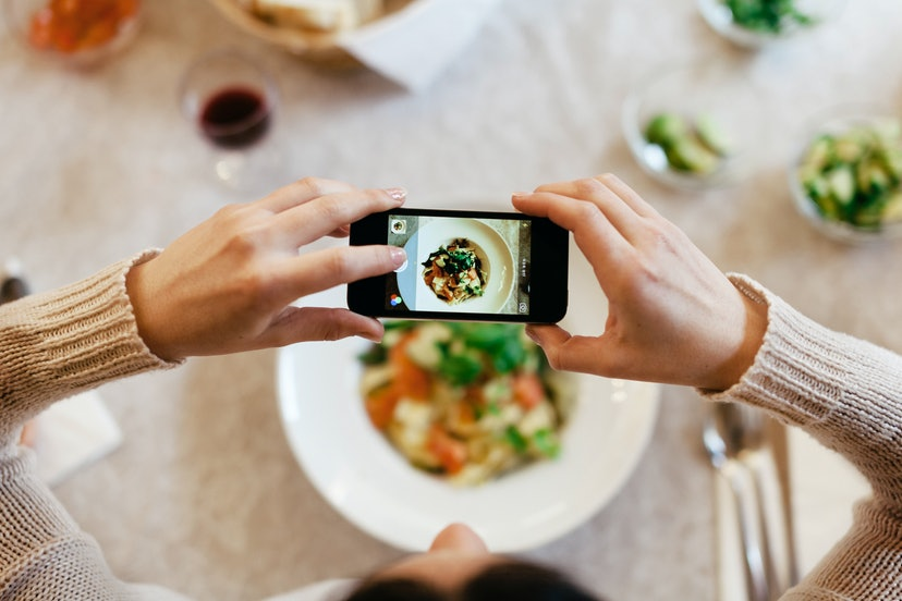 Bird's eye view of a woman taking a photo of her dinner with her smartphone. The plate is seen through the screen of the phone, while there is more food, cutlery, wine and bread on the table.