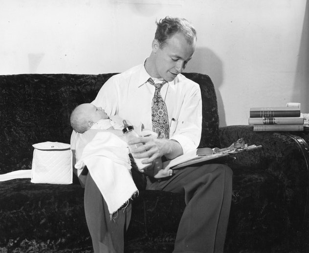GI Bill student Roy Estes feeds his son, Larry Allan, a bottle as he studies for one of his University of California classes, Berkeley, California, 1948. (Photo by Acme/United States Information Agency/PhotoQuest/Getty Images)