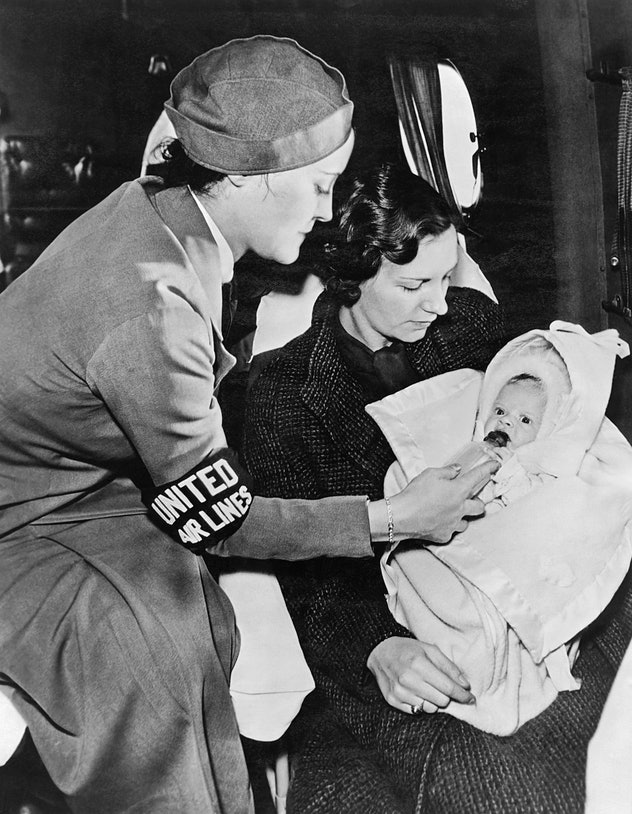 A United Airlines stewardess gives a baby a bottle on the airplane while the mother looks on, mid to late 1940s. (Photo by Underwood Archives/Getty Images)