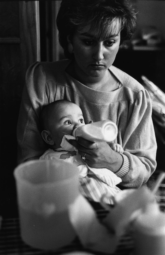 A mother feeding her baby from a bottle in Teeside, March 1986. (Photo by Steve Eason/Hulton Archive/Getty Images)