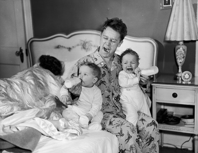circa 1955:  A father sits on the edge of his bed, yawning as he feeds twin babies bottles of milk. One of the babies cries as the mother sleeps behind them. The man wears pajamas.  (Photo by Harold M. Lambert/Lambert/Getty Images)