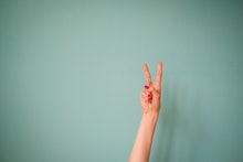 Hand peace sign in front of wall.