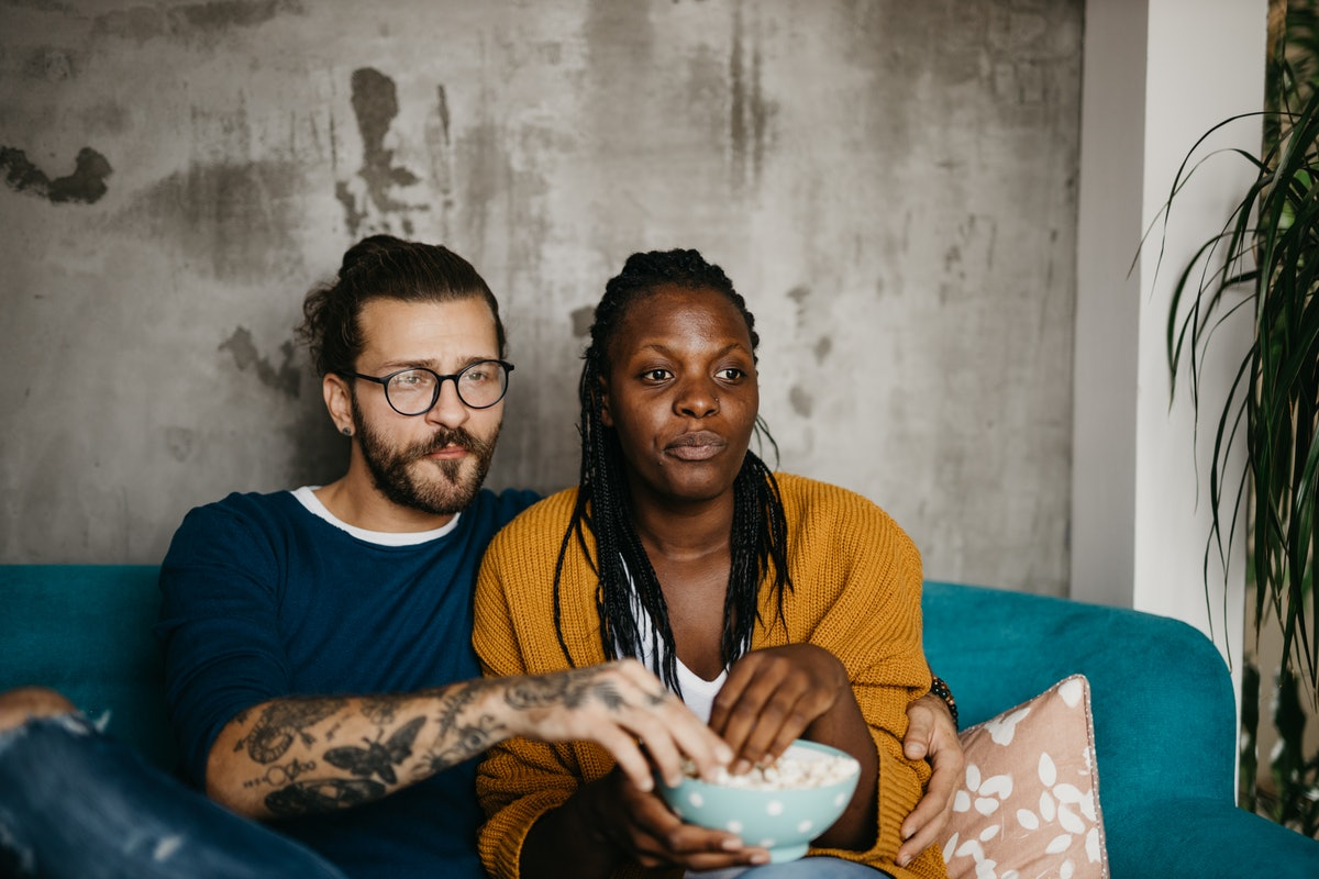 Young attractive couple sitting at home, eating popcorn and watching television